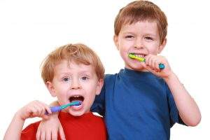 two little boys with tooth-brushes isolated on white