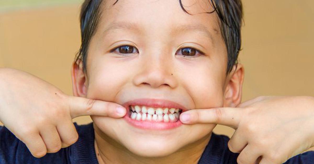A boy shows his teeth