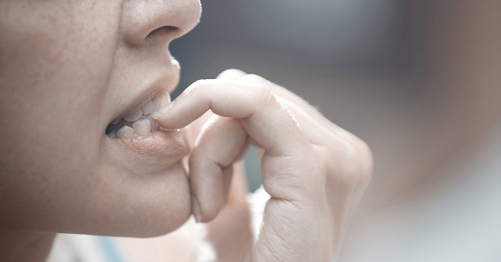 A woman biting her nail